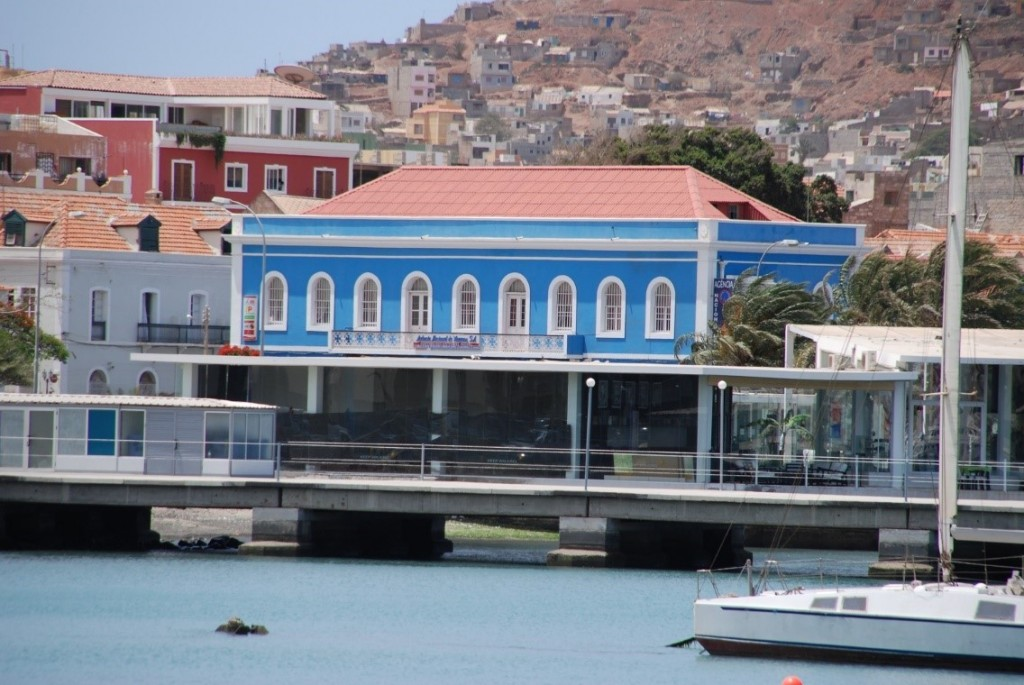 (Close-up of a section of Mindelo's seafront - Avenida da Republica - with newly built restaurant in the right of picture, refurbished properties in centre and left and behind them, rising up the hillsides, new residential constructions)