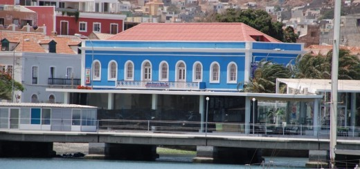 Close-up of a section of Mindelo's seafront - Avenida da Republica - with newly built restaurant in the right of picture, refurbished properties in centre and left and behind them, rising up the hillsides, new residential constructions