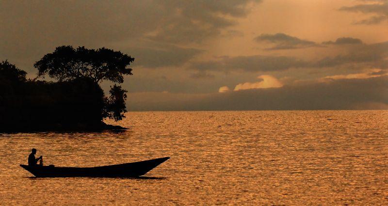 Fisherman on a lake at sunset